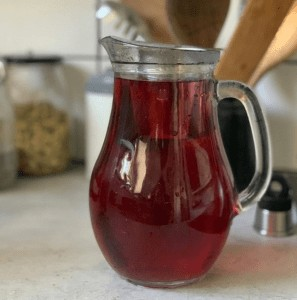 Röd surskölj med hibiskus i glaskanna